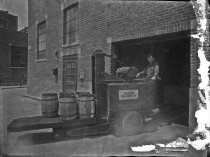 Image of Worker moving barrels at a garage or shop