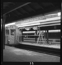 Image of Two men paint the awning at Willets Point while a 7 train pulls in.