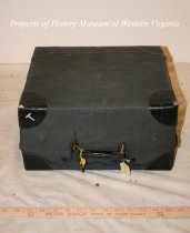 Image of Travel vanity case made of cardboard and leather with a protective canvas cover. Inside are many glass and plastic bottles and tools for applying make-up. 20th century, American.