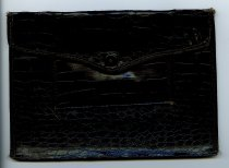 Image of Black Wallet - A black leather wallet, alligator skin pattern. One snap button to close wallet. One large pocket and one smaller pocket on the snap side of the wallet. Used to hold ration tokens during World War II.