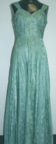 Image of Metalic brocade, aqua and silver, sleeveless, v-neckline, low back, flared skirt.  Worn by donor.