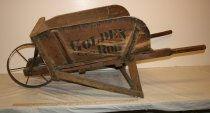 "Image of Wooden wheelbarrow - Wood and iron wheelbarrow with ""Golden Rod"" painted on the sides. The sides can be slid off to carry larger loads. 19th/20th century, American."