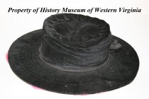 Image of Black velvet hat with silk flowers attached. - Wide brim, black velvet hat with three red/pink silk flowers sewn onto the underside of the brim. There is a black grosgrain ribbon and bow around the crown. ca. 1910, American.
