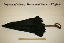 Image of Black silk-brocade parasol, cotton-lace scalloped-edge border, and carved wooden handle. - Black silk-brocade parasol with five-inch cotton-lace border with scalloped edge. Circa 1885-1890, American. The parasol has a carved wooden handle. The brocade covering the umbrella frame has a floral design.
