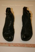 Image of Black leather shoes. - Pair of black leather men's shoes with black buttons and wooden soles. 20th century American.