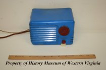 "Image of ""Detrola Pee-Wee"" plastic radio. - Small, blue plastic radio with red dials and white tab. Circa 1930-1949, American. The radio has an Art-Deco-type design. There is a large red dial imprinted with numbers 65 through 160. Beneath the dial is ""DETROLA."" Beneath this is another smaller red dial which sits above a white tab like structure. The reverse of the radio has a heavy cardboard with various sized openings for the four radio tubes housed behind it. Printed on the cardboard is the following: ""DETROLA PEE-WEE, 110 VOLT, A.C. D.C., License Notice On Reverse Side, No. 52199."" There are two brown, cloth covered wire cords coming from the radio."