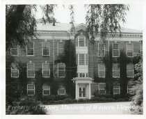 Image of Pleasants Hall -- Hollins College Campus - Black and white photograph of Pleasants Hall on the Hollins College campus. This is an ivy-draped three story brick building with a central entrance defined by double glass panelled doors.