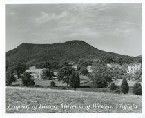 Image of Hollins College, back campus - A black and white photo of an aerial view of the back campus of Hollins College in Roanoke County, Virginia.  The photograph was taken in the summer and shows Tinker Mountain in the background. There are several academic buildings shown.