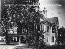 """Image of Residence of Thomas A. Kinsey,1510 Franklin Road SW - A black and white photograph (copy) of the residence of Thomas A. Kinsey, located at 1510 Franklin Road SW in Roanoke, Virginia circa 1925. The house is brick with a shingle roof. Shown are the front porch and trees, and a young girl in a light dress stands in the yard. The Roanoke City Directory for 1925 lists Mr. Kinsey's occupation as """"clerk."""""""