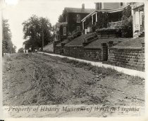 Image of Seventh Avenue, 1915 - A black and white photograph of Seventh Avenue, looking east from Franklin Road, taken in 1915. Shown are trees, a sidewalk, and several houses with stone walls fronting the sidewalk. A couple is seated on the porch of one of the homes on the right side of the photograph. Two other people are on the sidewalk, and a child stands in the street.