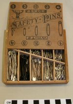 "Image of Wooden safety pin box - Wooden box with a sliding lid used to hold a variety of different sized safety pins.  The lid denotes sizes of ""black"" or ""white"" safety pins held in the different sections inside the box."