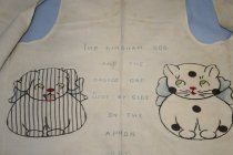 Image of Apron - Child's apron with an embroidered dog and cat, and a poem about the gingham dog and the calico cat.