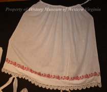 Image of Adult's Apron - Adult's apron. White cottom material with white lace at hem. Has bright red cross-stitched roses in a band on the bottom of the apron.