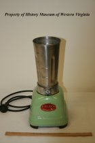 "Image of ""Stevens"" Electric Blender - Stainless steel, electric blender; ca 1946, American. The stainless steel holder is missing its lid; it sits on a green enameled metal base on which the following is printed within a red logo: ""MODEL 100, STEVENS, PAT. NO. 1,997_ _ 3, MADE IN U.S.A. _ _, JOHN OSTER MFG. Co. RACINE, WIS."" 