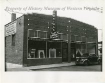Image of Sunnyside Awning & Tent Company - A black and white photograph of the new home of Sunnyside Awning & Tent Company, located at 119 Franklin Road in Roanoke, Virginia, taken after construction was completed. Displays of shades and venetian blinds are visible through the windows on the left, and a tent display is visible on the right. Note that the automobile in this photograph appears to be the same one partially visible in Object ID 1990.69.094.  Also note that this photograph appears to be identical to Object ID 1990.69.096.