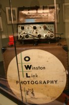 Image of Winston Link's sophisticated power supply (and a circuit diagram for it) are set up at the far left of the case. With this power supply, Link could fire up to 60 flashbulbs and trigger up to three cameras for any one photograph.
