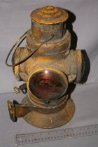 Image of Yellow hand held caboose lantern. One carrying handle. Top is hinged so you could light wick on the inside. One red glass lens, three amber glass lens, latch and hasp, latch turns to lock heap down. Wick adjustment turn key at back of lantern. One mounting bracket to mount on caboose.