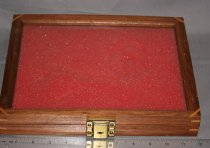 Image of Wooden display box with red sponge padding, hinged at top edge, lock on bottom edge. No key for lock. Back of box has 2005.08.02 (may be container that held 2005.08.02 - N&W lock:key).