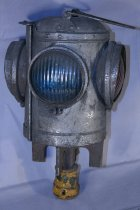 Image of Lantern with 2 red and 2 blue lens. reflectors, head has handle and opens. The body is cylindrical in shape. The base is meant to be attached to a post. Has been electrified.