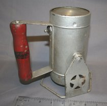 Image of Hand-held  railroad lantern. A slender cylindrical lantern. Painted silver with a movable stand. The red handle is on the bottom along with the switch for turning the light on and off. Star design stamped on stand sides, N&W inscription on side. Has been painted silver.
