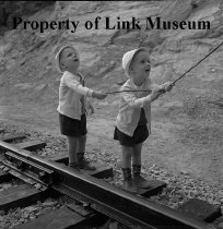 Image of Young Kids Flying A Kite By Tracks - Black and white negative of NW 563. Very young kids flying a kite by tracks; no locomotive.