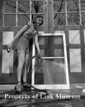 Image of Young Woman Washes Window - A young woman uses a waterhose and brush to wash a window.  (Client: Newell)