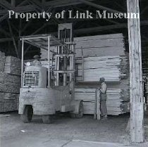 Image of umber Yard - Man next to pile of lumber and forklift (Client: Potlatch Forest Industries).