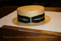 "Image of A Straw ""Boater"" Hat - A straw hat made in Italy for Keens Colonials. The hat is yellow straw with a 2"" black hat band with a silver and a gold stripe. It is fashioned into a bow on the left side."