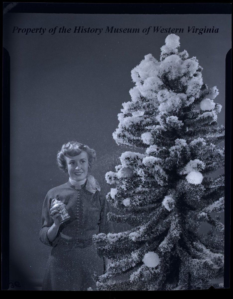 lady with make it snow spray can and christmas tree