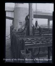 Image of 3 men and hoist Herbert Sandman, Knute Golden, Peder Abrahamsen, Arthur Nilsen