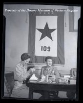 Image of 2 ladies sitting at table, banner with star in background