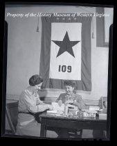 Image of 2 ladies at table, star flag behind them