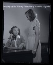 Image of 2 ladies in office , one with telephone