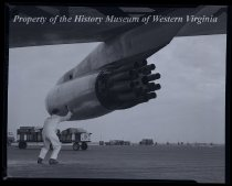 Image of Airplane wing with engine + man on tarmac, luggage cart in background