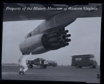 Image of Airplane wing with engine and man on tarmac