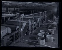 Image of 5 men inside manufacturing plant, barrels on right and sheets of material on rolls on left