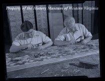 Image of 2 men working on design (carpet?)