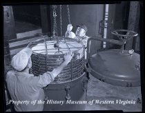 Image of 2 Men hoisting a round object