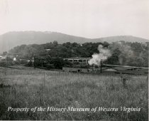 Image of A black and white photograph taken at Roanoke, Virginia showing pasture in the foreground, the railroad and buildings of Valley Lumber Corporation in the midddle ground, and Mill Mountain in the background. The elevated metal pipe extending from right to left across the image carried sawdust from the woodworking mill to an incinerator on the premises of the lumber company. Due to environmental considerations the incinerator, shown issuing smoke, was shut down some years ago.