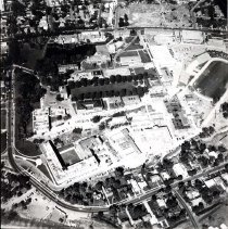 Image of UNRA-P1066-3 - Aerial of campus showing Evans Avenue and 9th Street on the southeast sides of campus; note cemetery at top of image. This aerial photograph shows the campus and surrounding neighborhood as they were in 1962. The historical Mackay Stadium depicted in this image is now the site of Hilliard Plaza where a plaque commemorating the stadium can be found. The cemetery depicted in the upper left portion of the image is now the location of Argenta Hall, Nye Hall, Canada Hall, and the Living Learning Community.