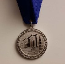 Image of UNRA-P3558-11 - Ribbon with the Nevada Writers Hall of Fame medal - displaying the side with the Getchell Library design (2012)