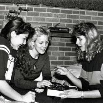 Image of UNRA-P3593-008 - Three female students share a box of chocolates in a dormitory room. This image was taken for the 1985 Student Handbook.