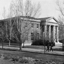 Image of UNRA-P221-10 - Two men walk past newly-planted trees near the Mackay School of Mines Building and the Quad. The Mackay School of Mines Building was originally built in 1908, funded by Clarence Mackay, for mining students. A second floor was added in 1926 by renowned Reno architect Frederic DeLongchamps. After being closed for many years and almost demolished, the building was listed on the National Register of Historic Places in 1982 and renovated again in 1988. Today the building houses the DeLaMare Library and the W.M. Keck Museum.