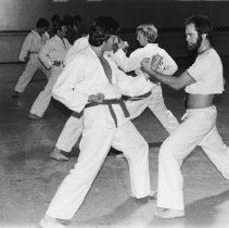 Image of UNRA-P913-01 - Students are posed in a sparring stance during karate class.