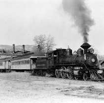 """Image of UNRS-P1992-01-0120 - Photograph of Locomotive No. 25 Making up a consist out of the Carson City Roundhouse of the V&T [Virginia and Truckee] Railway. 4-6-0 Baldwin (25016) built 1905. Dia. of cylinders 17 x 24. Dia. of drivers 60"""". Wt. 80,000 lbs. on drivers, 90,000 lbs. total. Sold in 1947 to R. K. O. Studio Hollywood. A little beauty of an engine. [Identification by] G. A. Sampson V. P. & G.M. 1950."""