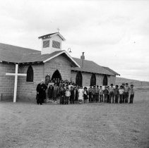 Image of UNRS-P1988-60-058 - Photograph of Gareth Hughes (Brother David) at a religious service at St. Mary's Episcopal Church, left, with Pyramid Lake reservation children in front of St. Mary's Episcopal Church in Nixon, Nevada