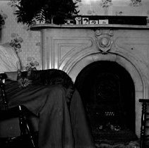 Image of UNRS-P1989-55-2949 - Photograph of Houses in Fallon; Interior; Ham; Woman in rocking chair by fireplace with cat on lap, second cat on chair nearby.