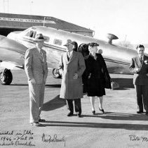 Image of UNRS-P1989-49-046 - Just landed in Elko [airplane and United Airlines Terminal in background]. December 21st, 1946. Vail to help dedicate Ranch Inn.  Newton Crumley, [left, Vail Pittman and Liz Pittman, center,]  Bob Miller [right].