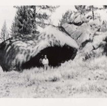 Image of UNRS-P1991-24-59 - Photograph of two men standing under large rock. Handwritten on verso: Summer camping site of Washo.  Underside of large rock, blackened by camp fires.  Sierra Nevada Foothills.  S. of Gardnerville, NV.  1937