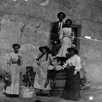 Image of UNRS-P1995-01-115 - Photograph of Women, girls, man and dog posed outside building; Monitor Valley.